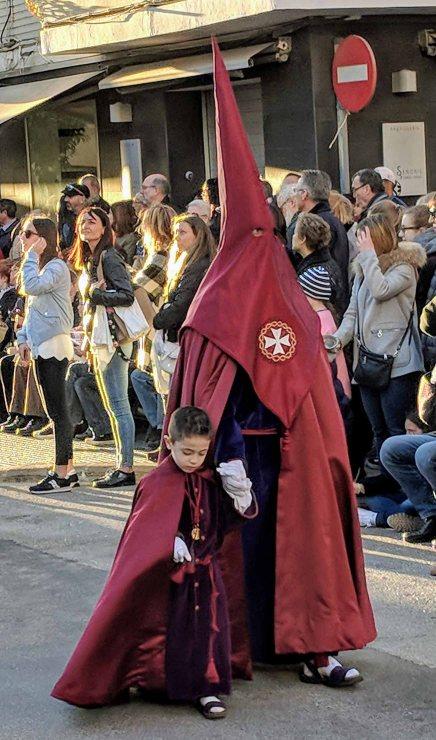 A robed participant in the colors of the Parroquia Nuestra Señora de los Ángeles