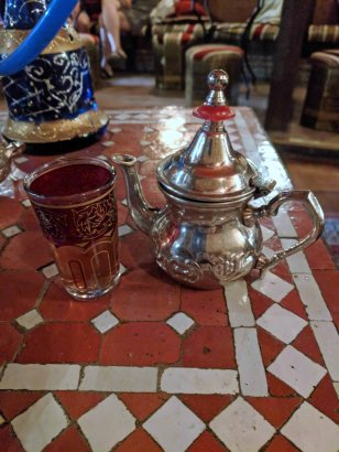 Moroccan tea served in a silver tea pot with a glass