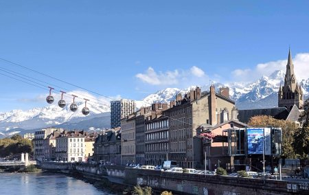"""The """"Les Bulles"""" cable cars in front of the glacier fed Isère river."""